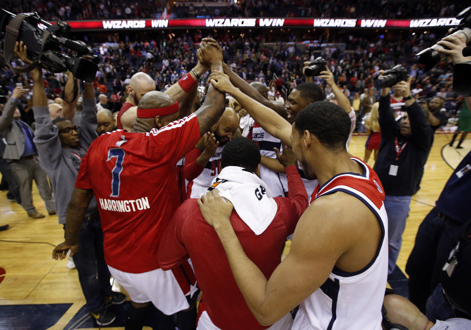 Photo - Washington Wizards celebrate at center court after an NBA basketball game against the Boston Celtics on Wednesday, April 2, 2014 in Washington. The Wizards won 118-92, and clinched a playoff berth. (AP Photo/Alex Brandon)