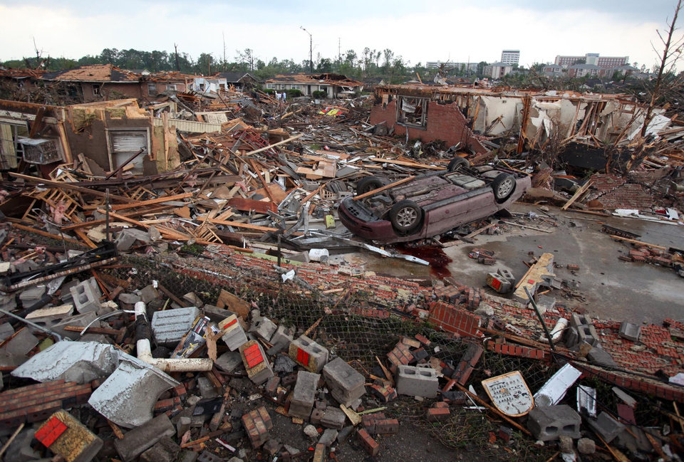Photo - A car lies overturns and buildings destroyed in Tuscaloosa, Ala., Wednesday, April 27, 2011. A wave of severe storms laced with tornadoes strafed the South on Wednesday; buildings across swaths of the university town were damaged or destroyed. (AP Photo/Tuscaloosa News, Dusty Compton)
