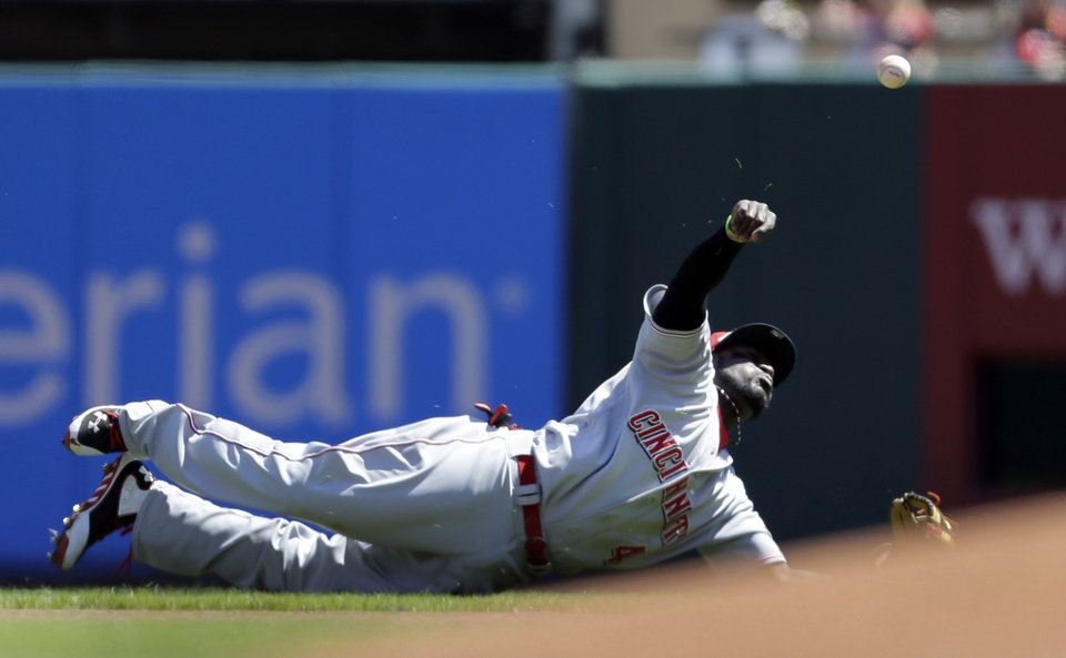 Photo - Cincinnati Reds second baseman Brandon Phillips throws St. Louis Cardinals' Kolten Wong out at first during the first inning of a baseball game Wednesday, April 9, 2014, in St. Louis. (AP Photo/Jeff Roberson)