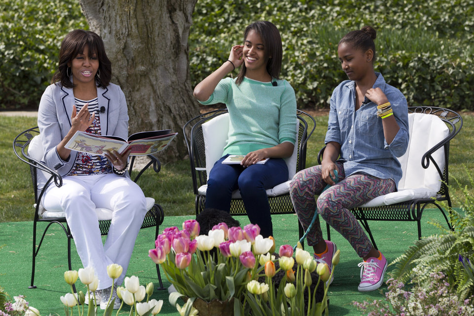 "First lady Michelle Obama, with daughters Malia and Sasha, reads the book ""Cloudy With A Chance of Meatballs"" to children as part of the annual White House Easter Egg Roll, Monday, April 1, 2013, on the South Lawn of the White House in Washington. (AP Photo/Jacquelyn Martin)"
