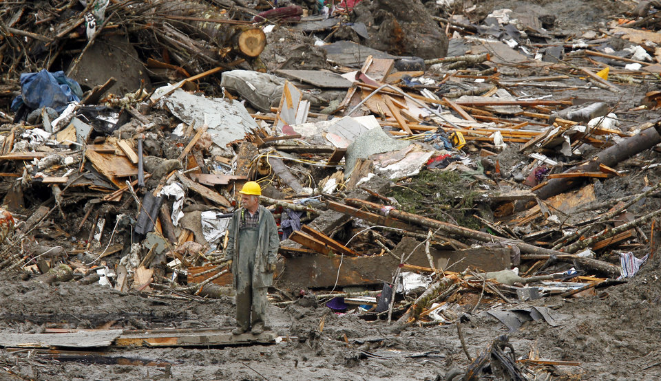 Photo - A searcher walks amidst a massive pile of debris at the scene of a deadly mudslide, Thursday, March 27, 2014, in Oso, Wash. The death toll is expected to rise considerably within the next two days as the Snohomish County Medical Examiner's Office catches up with the recovery effort, Snohomish County District 21 Fire Chief Travis Hots said Thursday. (AP Photo/The Herald, Mark Mulligan, Pool)