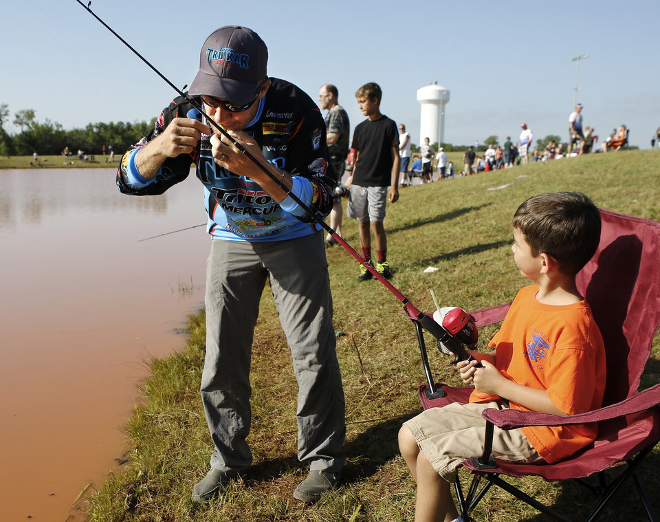 Photo - 2012 Bassmaster Angler of the Year Brent Chapman, from Lake Quivira, KS, uses his teeth to repair a small problem with the hook on the line of  6 year-old angler Tristan Perez' fishing pole.  Perez lives in Moore, with a problem in his line.  Moore hosted its annual kids fishing derby Saturday morning, July 27, 2013,  at Buck Thomas Park.  As part of the event this year, a charity called the Tackle the Storm Foundation handed out rods and reels to tornado victims. Several bass fishing pros from Oklahoma attended the event to help distribute the fishing equipment and share fishing tips with the young anglers. An event official  said about 250 children participated in the fishing derby. Photo  by Jim Beckel, The Oklahoman.