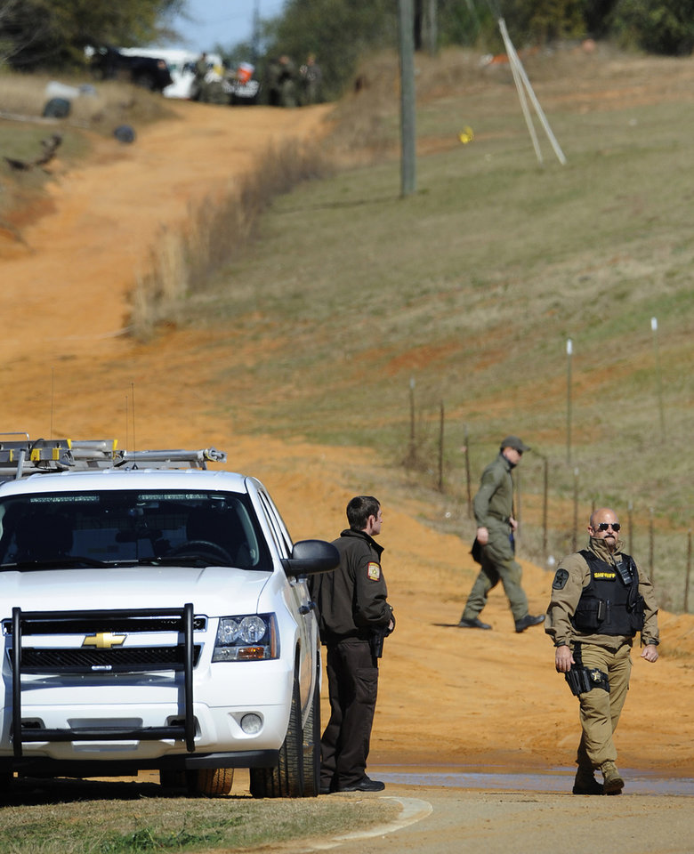Photo - Law officers at the Dale County hostage scene in Midland City, Ala. on Thursday, Jan. 31, 2013. A gunman holed up in a bunker with a 6-year-old hostage has kept law officers at bay since the standoff began when he killed a school bus driver and dragged the boy away, authorities said. (AP Photo/Montgomery Advertiser, Mickey Welsh)