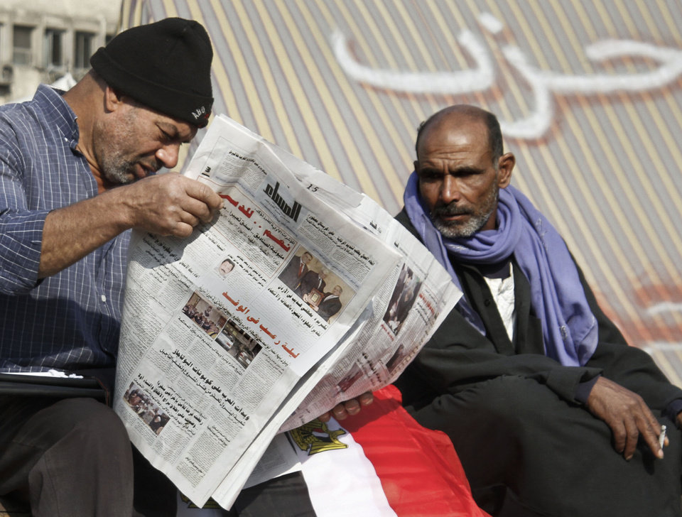 """Photo - An Egyptians protester reads a newspaper in Tahrir Square, the focal point of the Egyptian uprising, in Cairo, Sunday, Dec.16, 2012. Key Egyptian rights groups called Sunday for a repeat of the first round of the constitutional referendum, alleging the vote was marred by widespread violations. Islamists who back the disputed charter claimed they were in the lead with a majority of """"yes"""" votes. Arabic on the tent, background, reads,"""