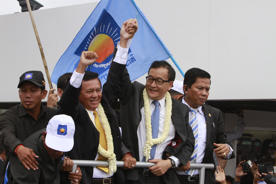 Photo - Sam Rainsy, center, president of Cambodia National Rescue Party (CNRP) holds hands with his party's Vice President Kem Sokha, second from left, on his arrival at Phnom Penh International Airport, in Phnom Penh, Cambodia, Friday, July 19, 2013. Thousands of cheering supporters greeted Cambodian opposition leader Rainsy as he returned from self-imposed exile Friday to spearhead his party's election campaign against well-entrenched Prime Minister Hun Sen. (AP Photo/Heng Sinith)