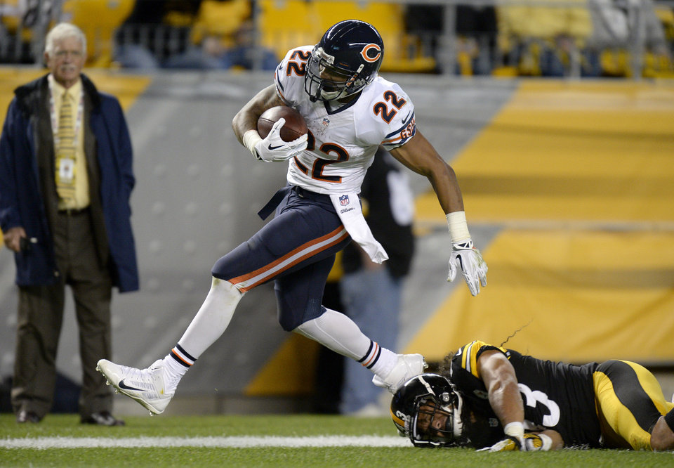 Photo - Chicago Bears running back Matt Forte (22), steps out of bounds after getting hit by Pittsburgh Steelers strong safety Troy Polamalu (43) on a long run in the first quarter of an NFL football game on Sunday, Sept. 22, 2013, in Pittsburgh. (AP Photo/Don Wright)