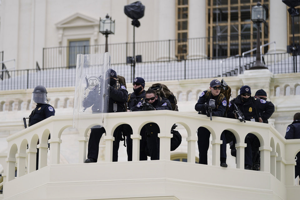 Photo - Police keep a watch on demonstrators who tried to break through a police barrier, Wednesday, Jan. 6, 2021, at the Capitol in Washington. As Congress prepares to affirm President-elect Joe Biden's victory, thousands of people have gathered to show their support for President Donald Trump and his claims of election fraud. (AP Photo/Julio Cortez)