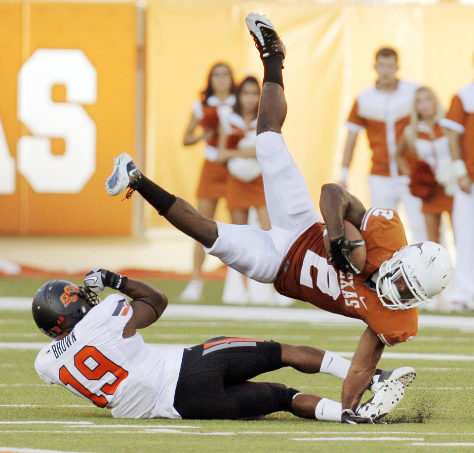 Texas' Fozzy Whittaker (2) gets tripped up by Oklahoma State's Brodrick Brown (19) in the second half during a college football game between the Oklahoma State University Cowboys (OSU) and the University of Texas Longhorns (UT) at Darrell K Royal-Texas Memorial Stadium in Austin, Texas, Saturday, Oct. 15, 2011. OSU won, 38-26. Photo by Nate Billings, The Oklahoman