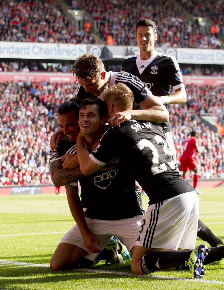 Southampton's Dejan Lovren, centre, celebrates with teammates after scoring against Liverpool during their English Premier League soccer match at Anfield Stadium, Liverpool, England, Saturday Sept. 21, 2013. (AP Photo/Jon Super)