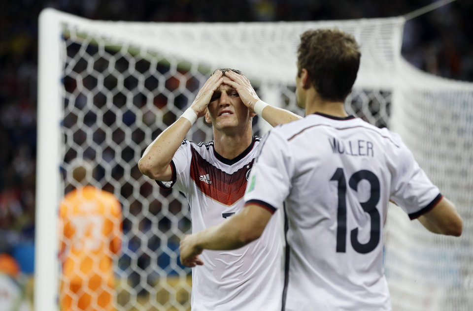 Photo - Germany's Bastian Schweinsteiger, left, reacts with his teammate Thomas Mueller after missing a near goal during the World Cup round of 16 soccer match between Germany and Algeria at the Estadio Beira-Rio in Porto Alegre, Brazil, Monday, June 30, 2014. (AP Photo/Kirsty Wigglesworth)