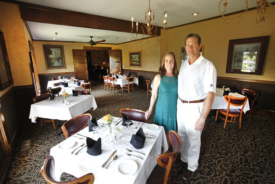 Photo -  Owners Lisa Janes and her husband, Gregg, stand in a dining room at Twelve Oaks Restaurant. Lisa Janes is the daughter of the late Bill Horn, who launched the restaurant 20 years ago.  Photo by David McDaniel, The Oklahoman     David McDaniel -  The Oklahoman