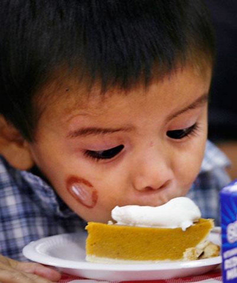 Photo -  Thayne Holtsoi, 2, puts his face next to his piece of pumpkin pie so he can lick the topping while eating with other members of his family at the annual Red Andrews Christmas Dinner at the Cox Convention Center in downtown Oklahoma City, Thursday, Dec. 25, 2008. BY JIM BECKEL, THE OKLAHOMAN