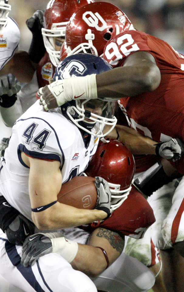 Photo - Oklahoma's Stacy McGee (92), top, and Oklahoma's Tom Wort (21) bring down Connecticut's Robbie Frey (44) during the Fiesta Bowl college football game between the University of Oklahoma Sooners and the University of Connecticut Huskies in Glendale, Ariz., at the University of Phoenix Stadium on Saturday, Jan. 1, 2011.  Photo by Bryan Terry, The Oklahoman