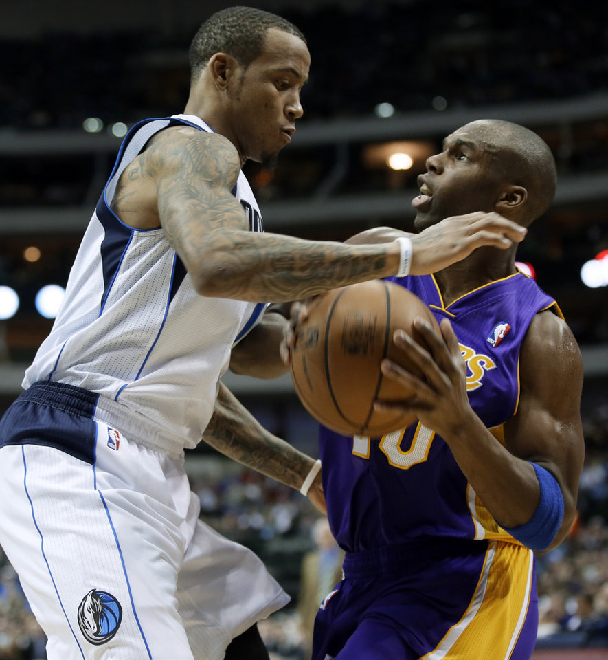Photo - Dallas Mavericks' Monta Ellis, left, defends as Los Angeles Lakers' Jodie Meeks (20) looks for an opening to the basket in the first half of an NBA basketball game, Tuesday, Jan. 7, 2014, in Dallas. (AP Photo/Tony Gutierrez)