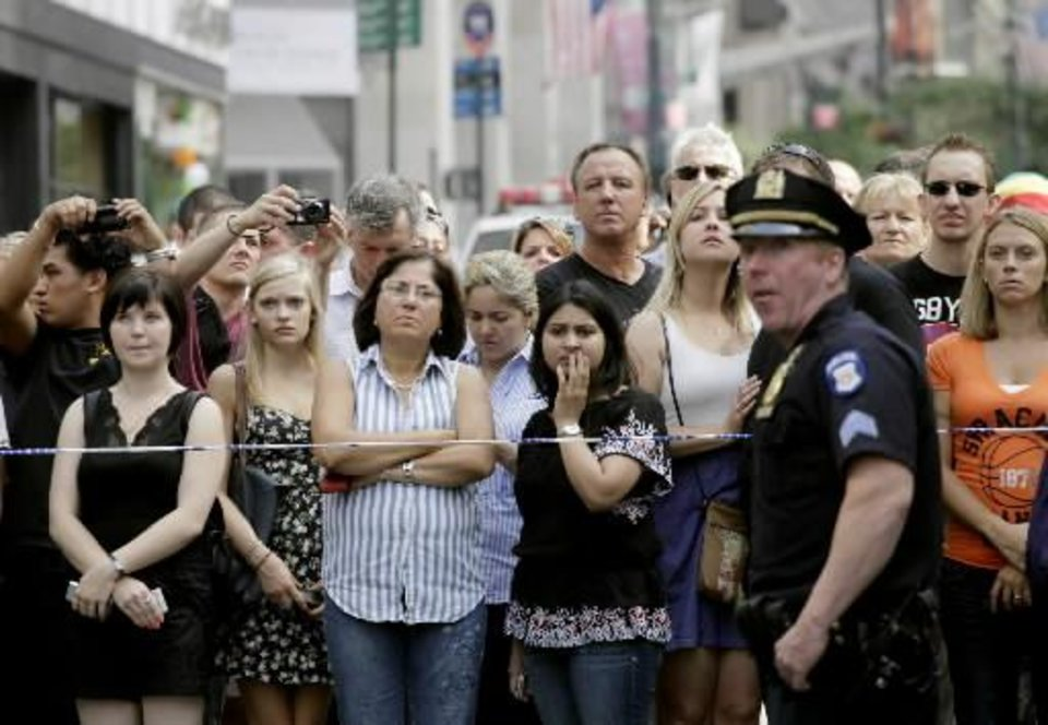 Photo - Bystanders and a police officer stand on Fifth Avenue to view the scene after a multiple shooting outside the Empire State Building, Friday, Aug. 24, 2012, in New York. At least four people were shot on Friday morning and the gunman was dead, New York City officials said. A witness said the gunman was firing indiscriminately. Police said as many as 10 people were injured, but it is unclear how many were hit by bullets. A law enforcement official said the shooting was related to a workplace dispute. The official spoke on condition of anonymity because the investigation was ongoing. (AP Photo/Mark Lennihan)