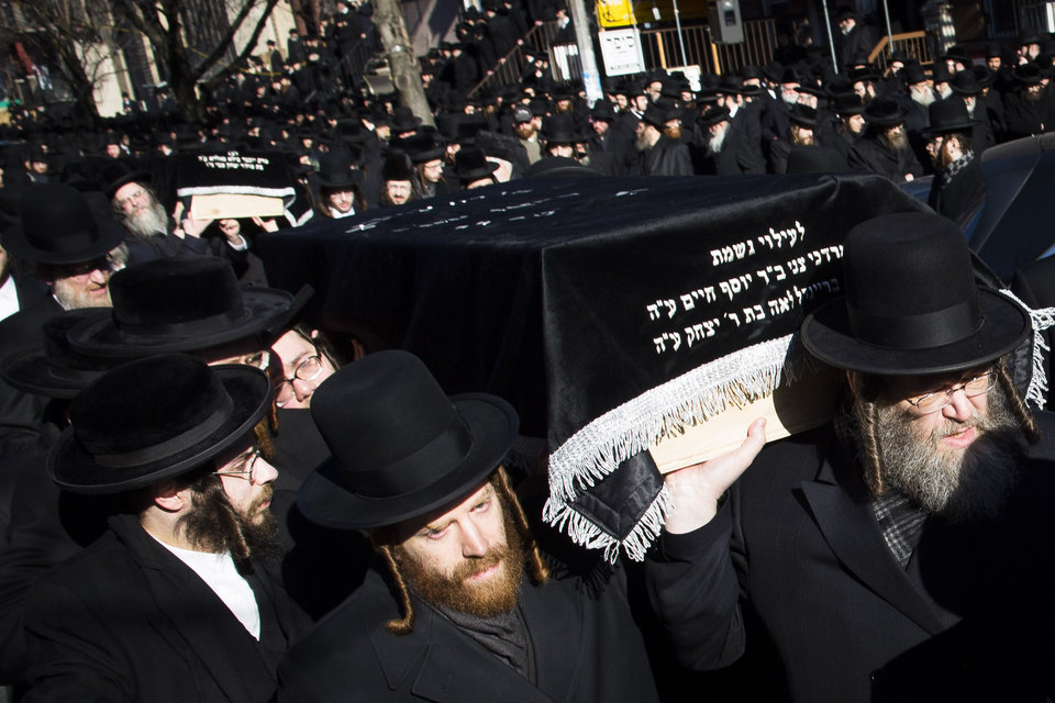 Photo - Members of the Satmar Orthodox Jewish community carry the coffins of two expectant parents who were killed in a car accident, Sunday, March 3, 2013, in the Brooklyn borough of New York. A  driver struck the car early Sunday morning, killing both parents while their baby, who was born prematurely, survived and is in critical condition. (AP Photo/John Minchillo)
