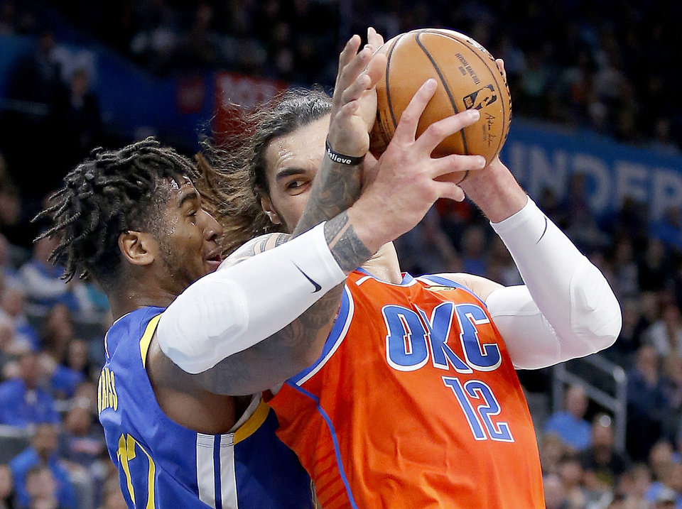 Photo - Oklahoma City's Steven Adams (12) goes to the basket as he is defended by Golden State's Marquese Chriss (32) during the NBA game between the Oklahoma City Thunder and Golden State Warriors at Chesapeake Energy Arena,  Sunday, Oct. 27, 2019. Thunder won 120-92.[Sarah Phipps/The Oklahoman]