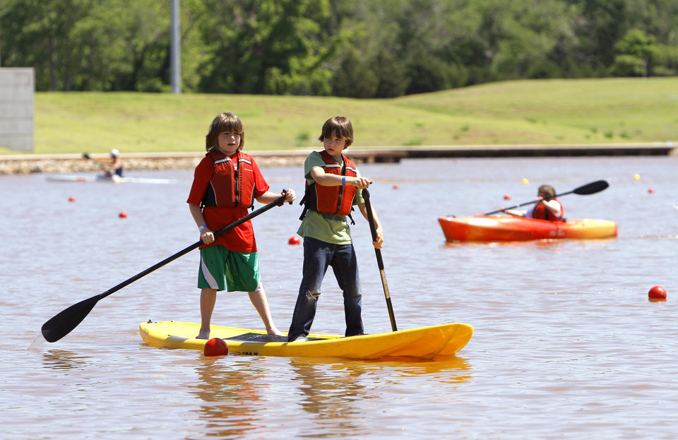 Photo - Dylan Kemether, 8, and Camden Sexton, 9, paddle during the Paddle Now! Youth Experience on the Oklahoma River,  Saturday, April 21, 2012. Photo by Sarah Phipps, The Oklahoman.
