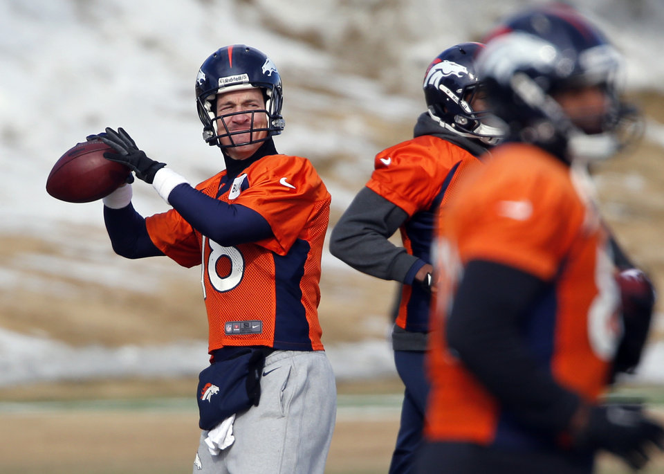 Photo - Denver Broncos quarterback Peyton Manning (18) throws during practice for the football team's NFL playoff game against the San Diego Chargers at the Broncos training facility in Englewood, Colo., on Friday, Jan. 10, 2014. (AP Photo/Ed Andrieski)
