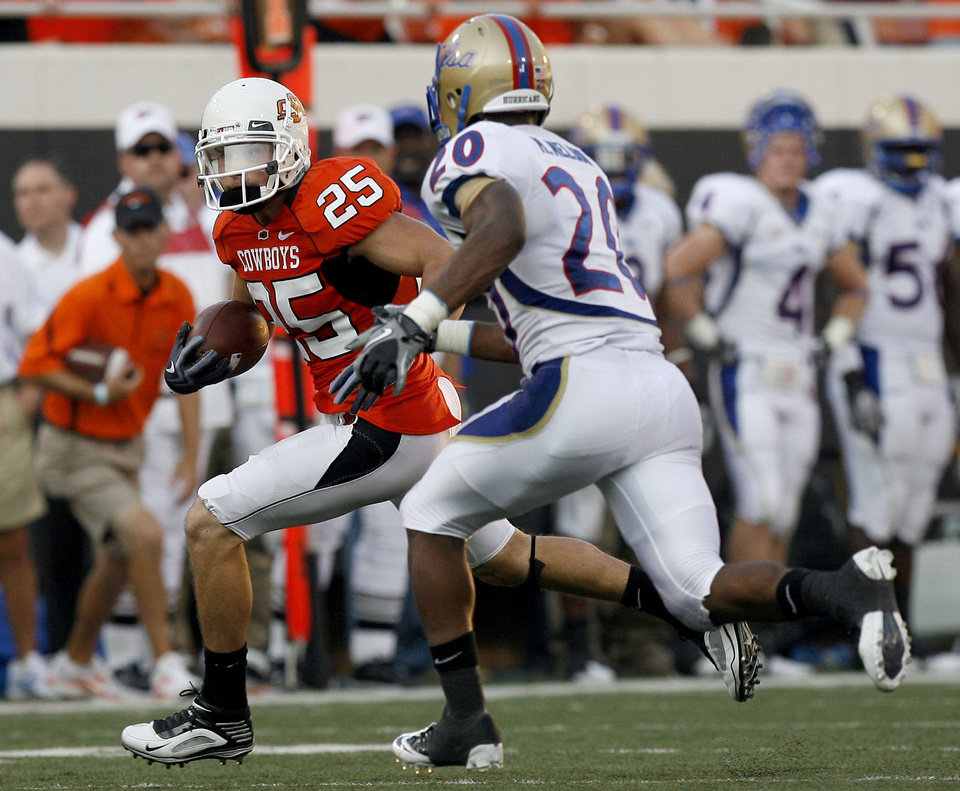 Oklahoma State wide receiver Josh Cooper (25) tries to get past Tulsa's Marco Nelson (20) during the college football game between the University of Tulsa (TU) and Oklahoma State University (OSU) at Boone Pickens Stadium in Stillwater, Oklahoma, Saturday, September 18, 2010. Photo by Sarah Phipps, The Oklahoman