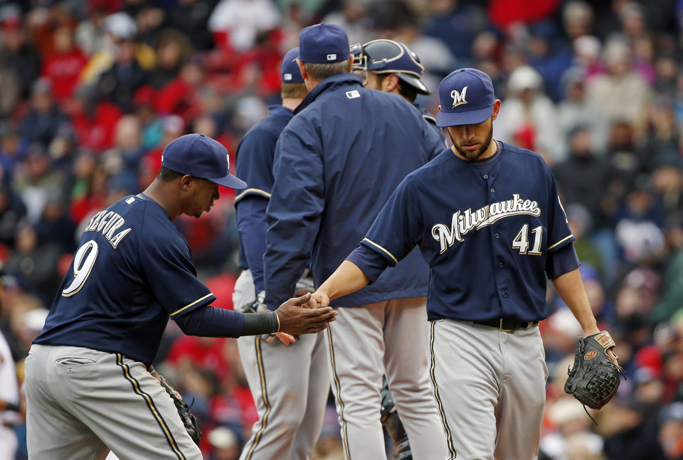 Photo - Milwaukee Brewers starting pitcher Marco Estrada (41) receives a handshake from shortstop Jean Segura (9) as he is relieved in the sixth inning of a baseball game against the Boston Red Sox at Fenway Park in Boston, Friday, April 4, 2014. (AP Photo/Elise Amendola)