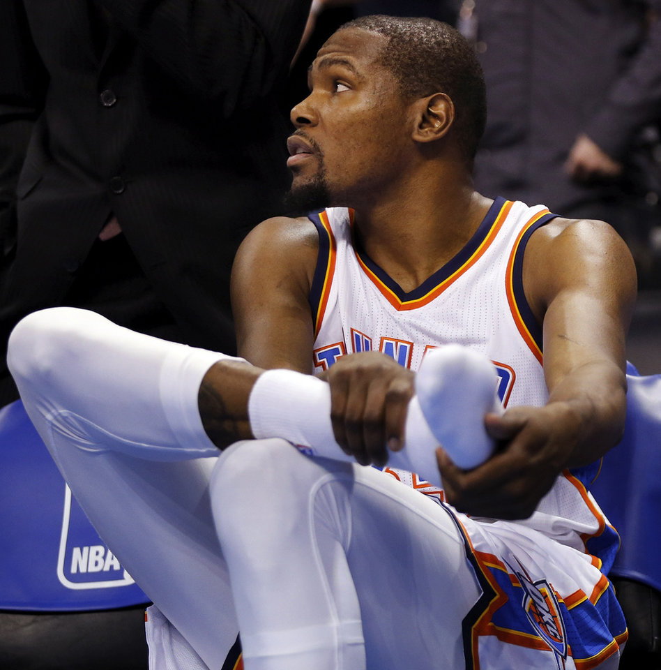 Photo - Oklahoma City's Kevin Durant (35) rubs his right foot after taking a seat on the bench with more than two minutes left in the fourth quarter during an NBA basketball game between the Oklahoma City Thunder and the Dallas Mavericks at Chesapeake Energy Arena in Oklahoma City, Thursday, Feb. 19, 2015. Oklahoma City won 104-89. Photo by Nate Billings, The Oklahoman