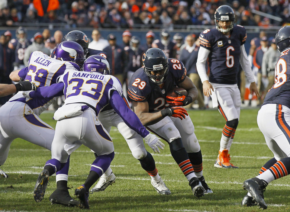 Chicago Bears running back Michael Bush (29) rushes for a touchdown against Minnesota Vikings safety Jamarca Sanford (33) and defensive end Jared Allen (69) in the first half of an NFL football game in Chicago, Sunday, Nov. 25, 2012. In the bAckground is Bears quarterback Jay Cutler (6). (AP Photo/Charles Rex Arbogast)