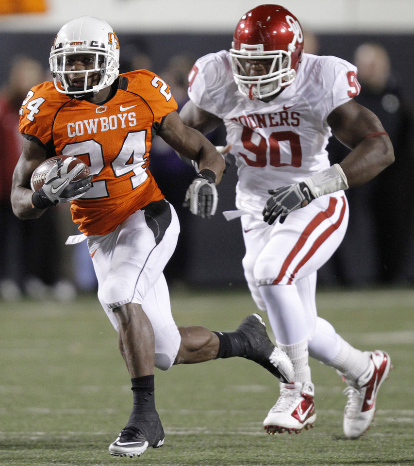 Photo - Oklahoma State's Kendall Hunter (24) runs past Oklahoma's David King (90) during the Bedlam college football game between the University of Oklahoma Sooners (OU) and the Oklahoma State University Cowboys (OSU) at Boone Pickens Stadium in Stillwater, Okla., Saturday, Nov. 27, 2010. Photo by Chris Landsberger, The Oklahoman