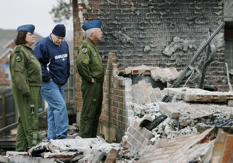 Photo - Roger Burgwyn, center and two fellow members of the Canadian Air Force  look at the remains of his home  Friday morning, April 10, 2009 which was destroyed in Thursday's wildfires.  At right is CWO James Dawson.  Photo by Jim Beckel, The Oklahoman
