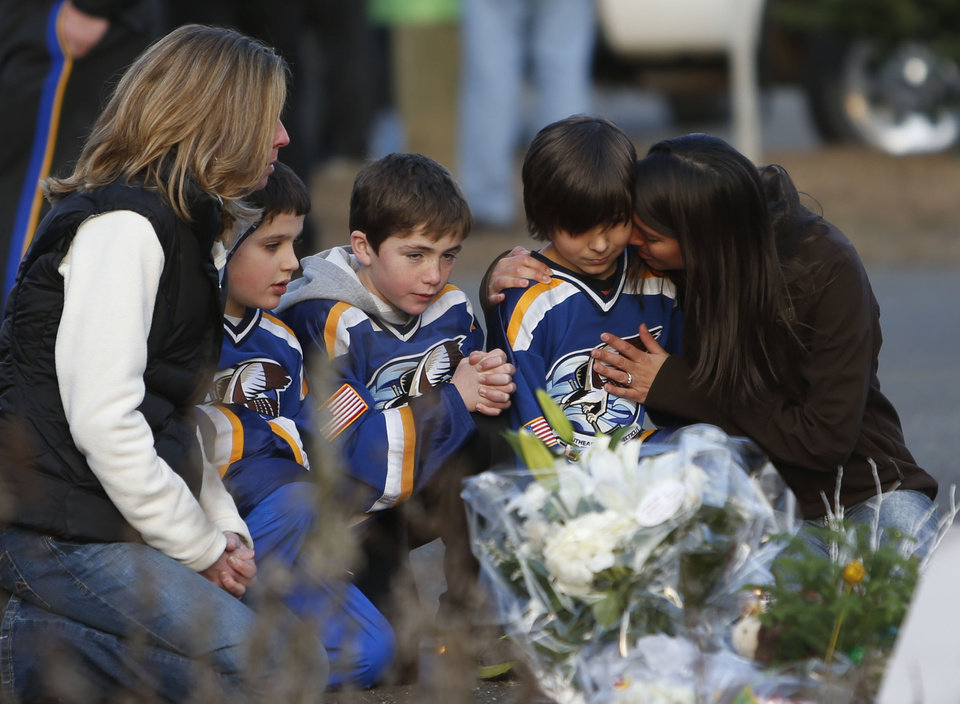 Photo - From left, Jean Bradley, Steven Turchetta, 9, Jean's son Matthew Bradley, 9, Ashton Baltes, 10, and his mother Elonda Baltes pay their respects at a memorial for shooting victims near Sandy Hook Elementary School, Saturday, Dec. 15, 2012 in Newtown, Conn.  A gunman walked into Sandy Hook Elementary School in Newtown Friday and opened fire, killing 26 people, including 20 children.  The three friends play on the same hockey team, and wanted to visit the memorial Saturday after having played a hockey game nearby. (AP Photo/Jason DeCrow) ORG XMIT: CTJD113