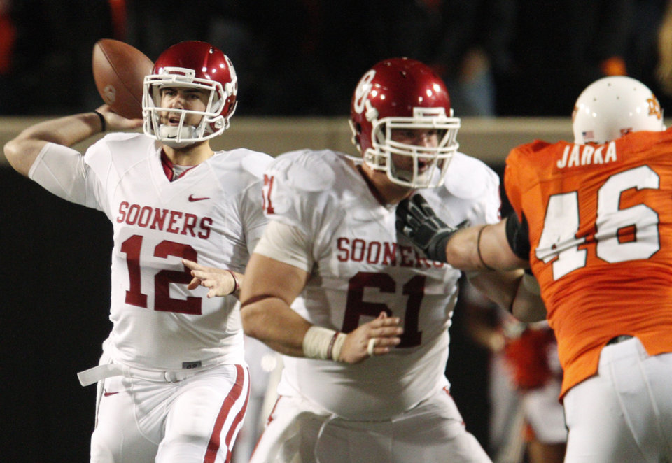 Photo - Oklahoma's Landry Jones (12) throwss a pass during the Bedlam college football game between the University of Oklahoma Sooners (OU) and the Oklahoma State University Cowboys (OSU) at Boone Pickens Stadium in Stillwater, Okla., Saturday, Nov. 27, 2010. Photo by Bryan Terry, The Oklahoman