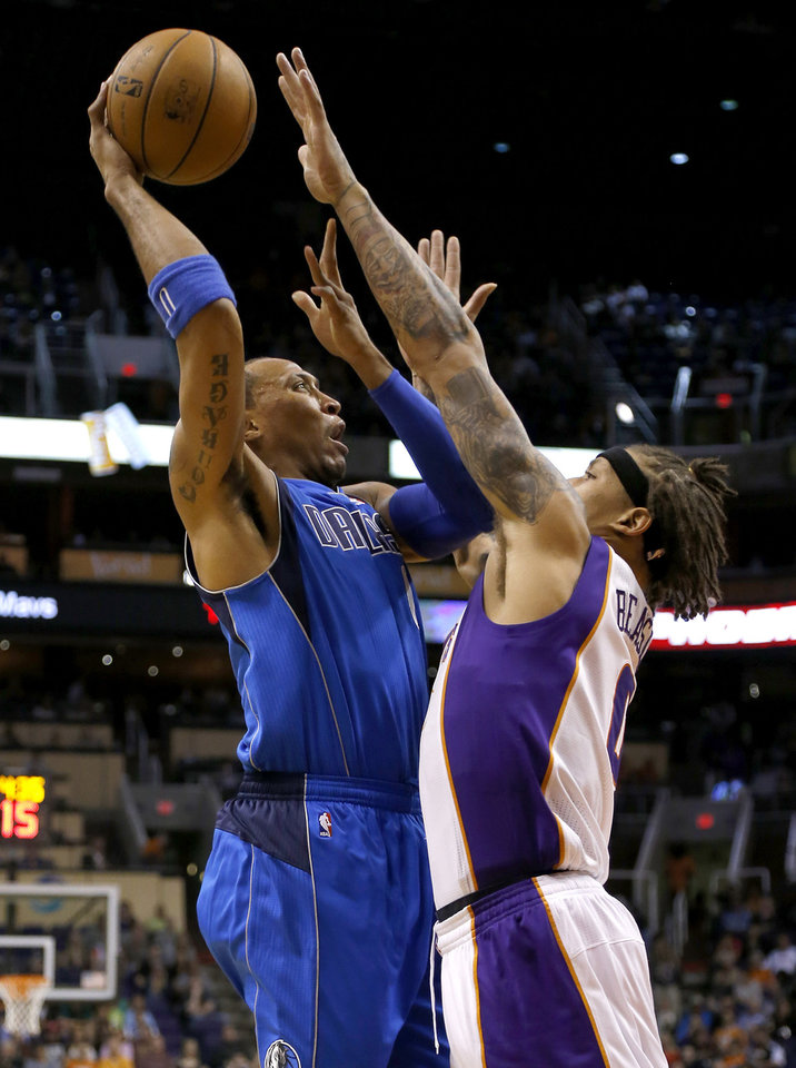 Dallas Mavericks' Shawn Marion, left, shoots over Phoenix Suns' Michael Beasley during the first half of an NBA basketball game Friday, Feb. 1, 2013, in Phoenix. (AP Photo/Matt York)