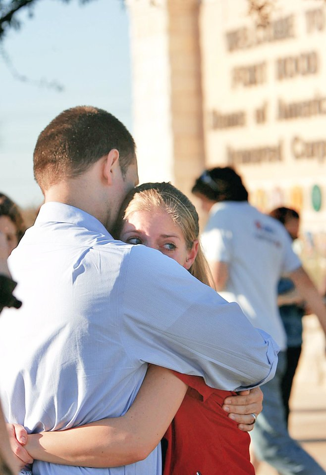 Photo - Daniel Clark hugs and comforts his wife, Rachel, on Thursday outside of the main gate of Fort Hood near Killeen, Texas. Daniel's daughter, Madeline, 5, was in an elementary school on the post, which was locked down after a shooting happened. AP PHOTO
