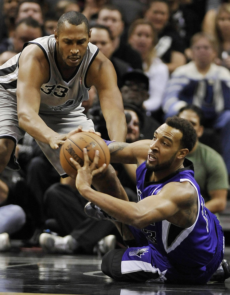 Sacramento Kings forward Derrick Williams, right, fights for the loose ball against San Antonio Spurs forward Boris Diaw, of France, during the first half of an NBA basketball game on Sunday, Dec. 29, 2013, in San Antonio. (AP Photo/Darren Abate)