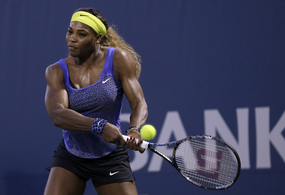 Photo - Serena Williams returns the ball to Ana Ivanovic, from Serbia, during the first set of their match in the Bank of the West Classic tennis tournament in Stanford, Calif., Friday, Aug. 1, 2014. (AP Photo/Jeff Chiu)