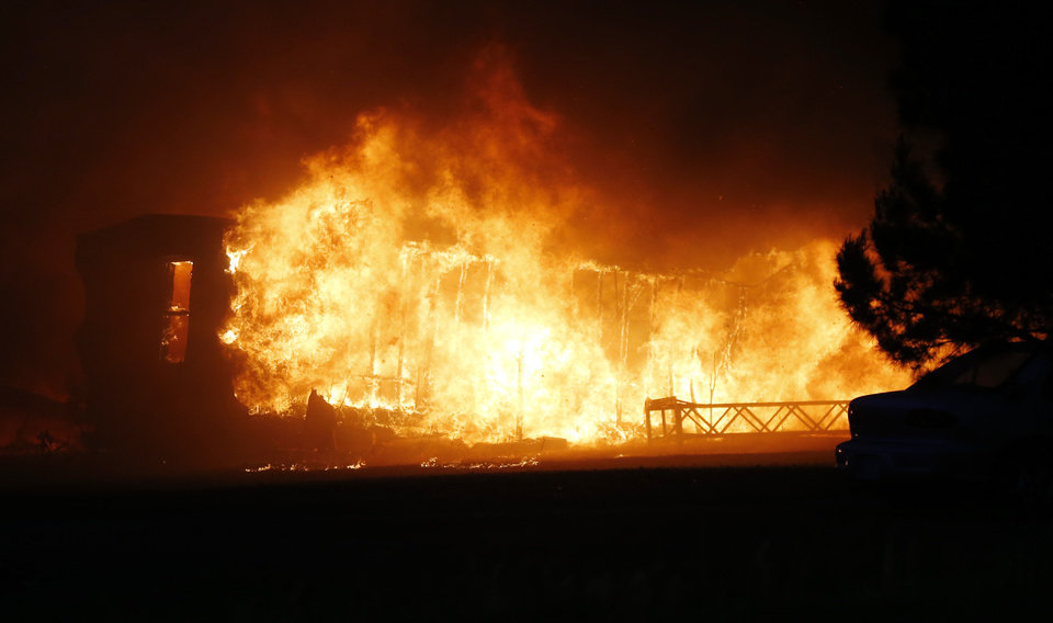 Photo - A mobile home burns at a mobile home park near Prairie Grove and Douglas during wildfires in south Logan County, Sunday, May 4, 2014. Photo by Nate Billings, The Oklahoman