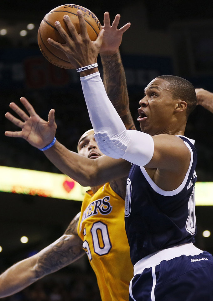 Photo - Oklahoma City's Russell Westbrook (0) takes the ball past LA's Robert Sacre (50) during an NBA basketball game between the Los Angeles Lakers and the Oklahoma City Thunder at Chesapeake Energy Arena in Oklahoma City, Friday, Dec. 13, 2013. Photo by Nate Billings, The Oklahoman