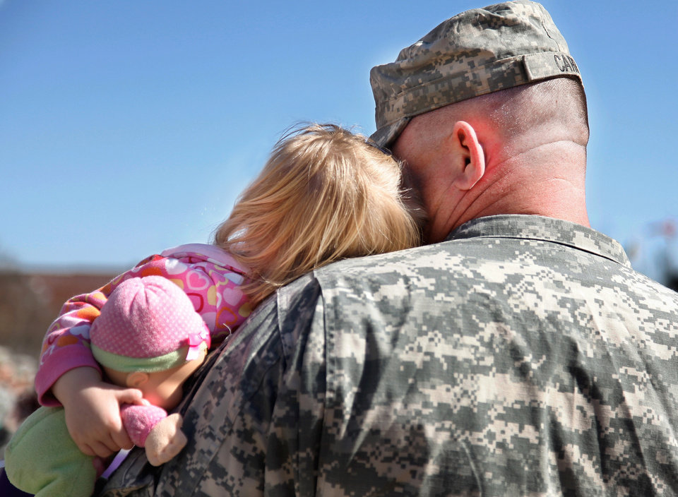 Photo - Clutching her doll, Anna Belle Carr, 20 months, leans her head against her dad's face as his family gathers outside the Oklahoma City Arena after the 45th Infantry Brigade Combat Team Deployment Ceremony in downtown Oklahoma City, Wednesday, Feb. 16, 2011. Capt. Donald Carr, of Blanchard, will be leaving on his sixth deployment.   Photo by Jim Beckel, The Oklahoman