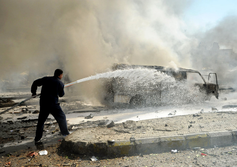 Photo - This photo released by the Syrian official news agency SANA, shows a Syrian fire fighter extinguishing burning cars after a huge explosion that shook central Damascus, Syria, Thursday, Feb. 21, 2013. A car bomb shook central Damascus on Thursday, exploding near the headquarters of the ruling Baath party and the Russian Embassy, eyewitnesses and opposition activists said. (AP Photo/SANA)