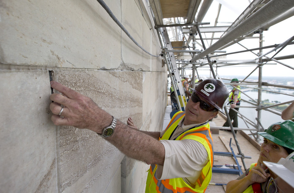 Photo - FILE - In this June 2, 2013 file photo, Bob Collie, project manager with Perini Management Services, puts his finger in a crack of the Washington Monument at the 491-foot level of the scaffolding surrounding the monument, in Washington. The monument, which sustained damage from an earthquake in August 2011, will re-open to the public on Monday, May 12, 2014. (AP Photo/Alex Brandon, File)