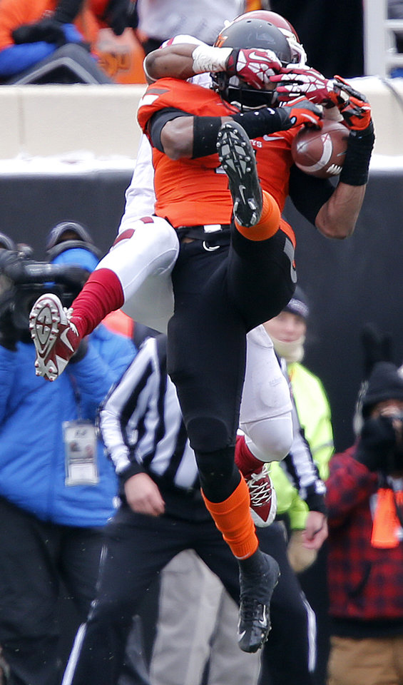 Oklahoma State's Justin Gilbert (4) breaks up a pass for Oklahoma's Lacoltan Bester (11) during the Bedlam college football game between the Oklahoma State University Cowboys (OSU) and the University of Oklahoma Sooners (OU) at Boone Pickens Stadium in Stillwater, Okla., Saturday, Dec. 7, 2013. Photo by Chris Landsberger, The Oklahoman
