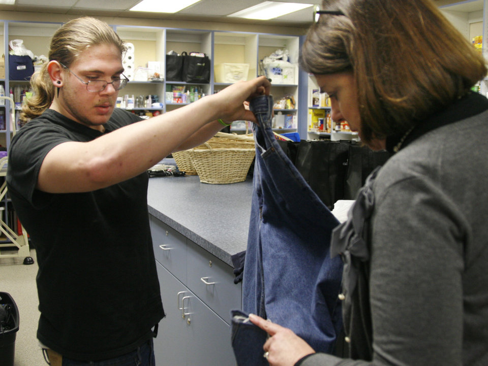 Sonny Qualm, senior at Oklahoma Centennial High School, picks out a pair of jeans Thursday with the assistance of Debbie Forshee, chief executive at Youth Services of Oklahoma County. Photo by Zeke Campfield, The Oklahoman