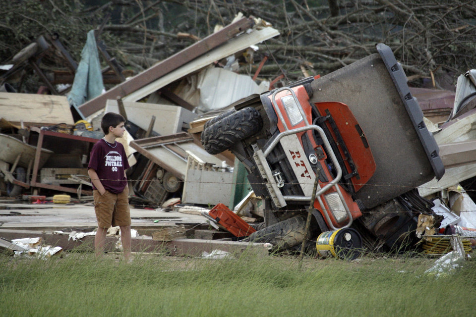 Photo - A young resident surveys the damage to a home near Bond, Miss., Wednesday, April 27, 2011. Several tornadoes hit  in the state resulting in number of deaths. (AP Photo/Rogelio V. Solis)