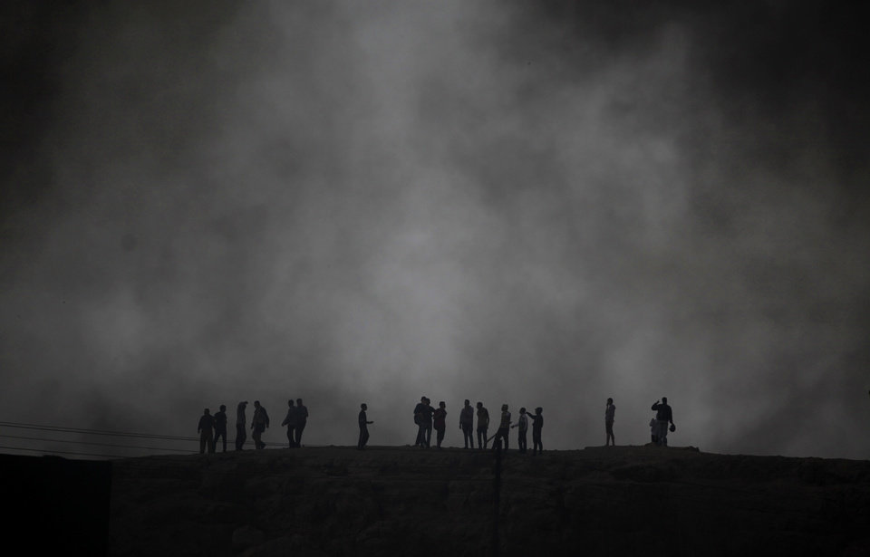 Photo - FILE - In this Friday, March 22, 2013 file photo, Egyptians are seen through black smoke as they stand on top of a hill during clashes between supporters and opponents of Egypt's powerful Muslim Brotherhood near the Islamist group's headquarters in Cairo, Egypt. Egypt's Islamist president makes good on vows of action against opponents, as the top prosecutor issues arrest warrants against five prominent activists and summons opposition politicians for questioning over weekend clashes between the Muslim Brotherhood and protesters. (AP Photo/Khalil Hamra, File)