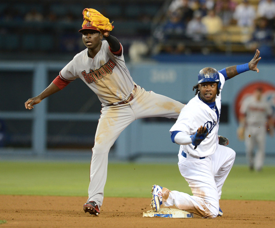 Photo - Los Angeles Dodgers' Hanley Ramirez and Arizona Diamondbacks shortstop Didi Gregorius wait for the call from the umpire as Ramirez is called safe on a steal in the sixth inning of a baseball game Saturday, June 14, 2014, in Los Angeles. (AP Photo/Jayne Kamin-Oncea)