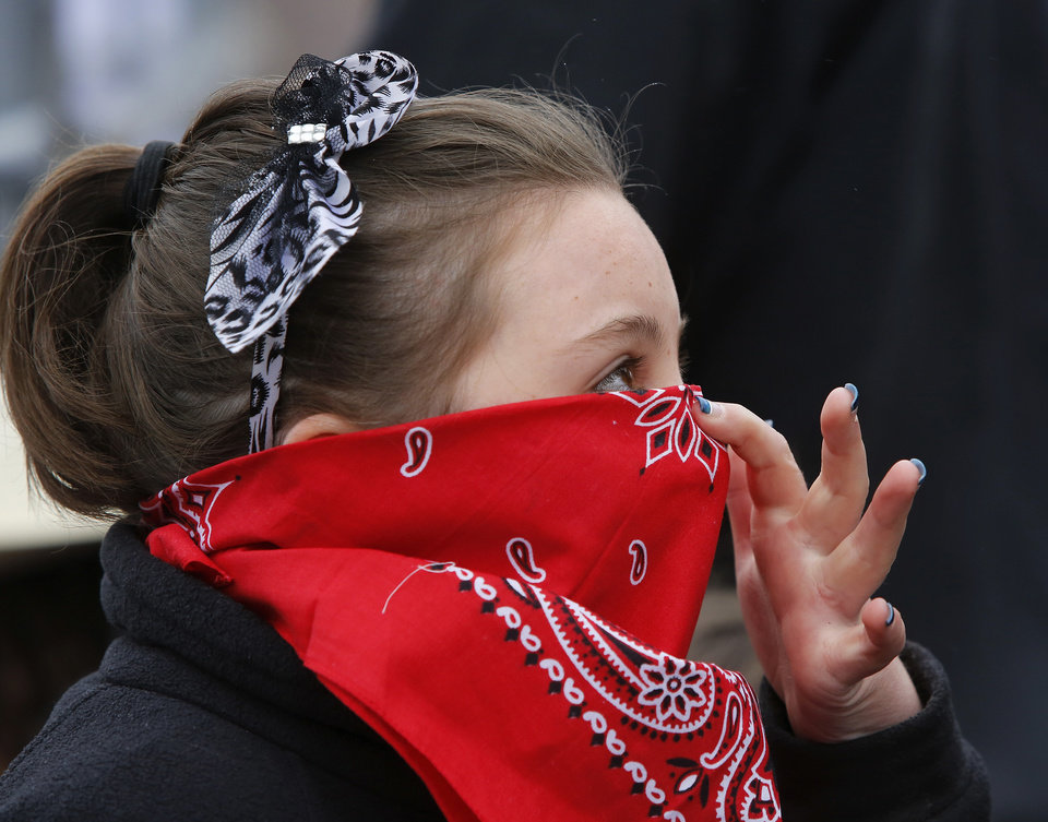 "Jenna Paterson, 11, uses her bandana to cover her mouth and nose in an attempt to keep her face warm. Peterson came with several members of her family and their friends from Konawa. Children with their parents endured cold temperatures and intermittent rain to come to the grounds of the Oklahoma History Center on Saturday, March 23, 2013, to participate in the 3rd annual Cowboy Round-up,  billed to be a  ""rendezvous with adventure.""  Cowboys and chuck wagons were on hand to bring the cattle drive era to life for visitors of all ages. Special activities included pony rides, stick-horse races, roping demonstrations, branding,  a medicine man show, biscuits made from scratch and cooked in Dutch ovens, and a chance for children to make a braided rope they could take with them as a souvenir.  Youth were encouraged to dress the part as many did, wearing boots, vests, bandanas, chaps,and cowboy hats.    Photo by Jim Beckel, The Oklahoman"