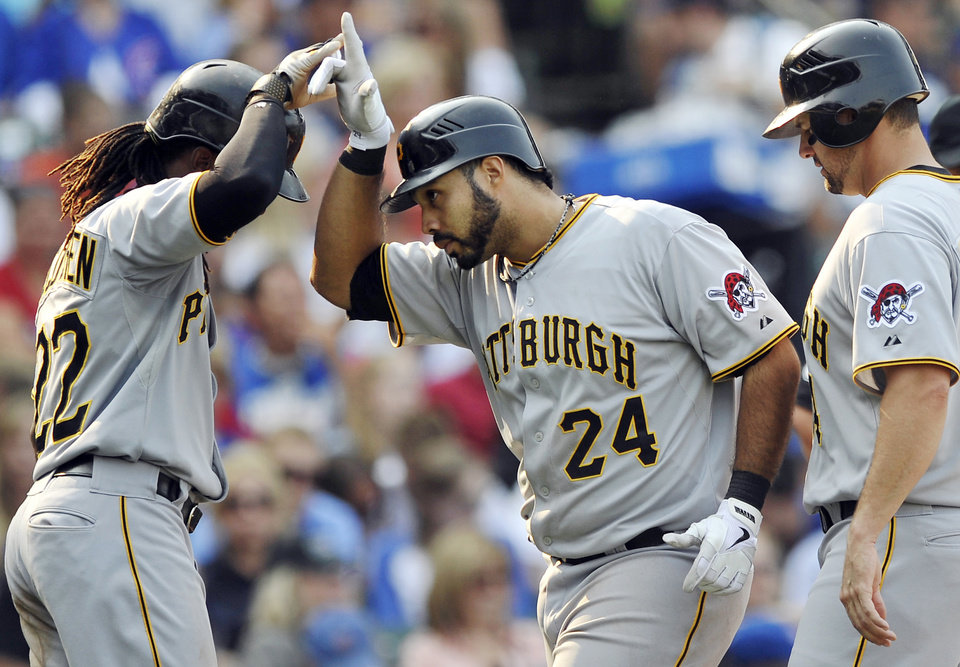 Photo -   Pittsburgh Pirates' Pedro Alvarez (24) celebrates with Andrew McCutchen left, while Gabby Sanchez, right, watches after Alvarez hit a three-run home run in the sixth inning during a baseball game against the Chicago Cubs in Chicago, Sunday, Sept. 16, 2012. Chicago won 13-9. (AP Photo/Paul Beaty)
