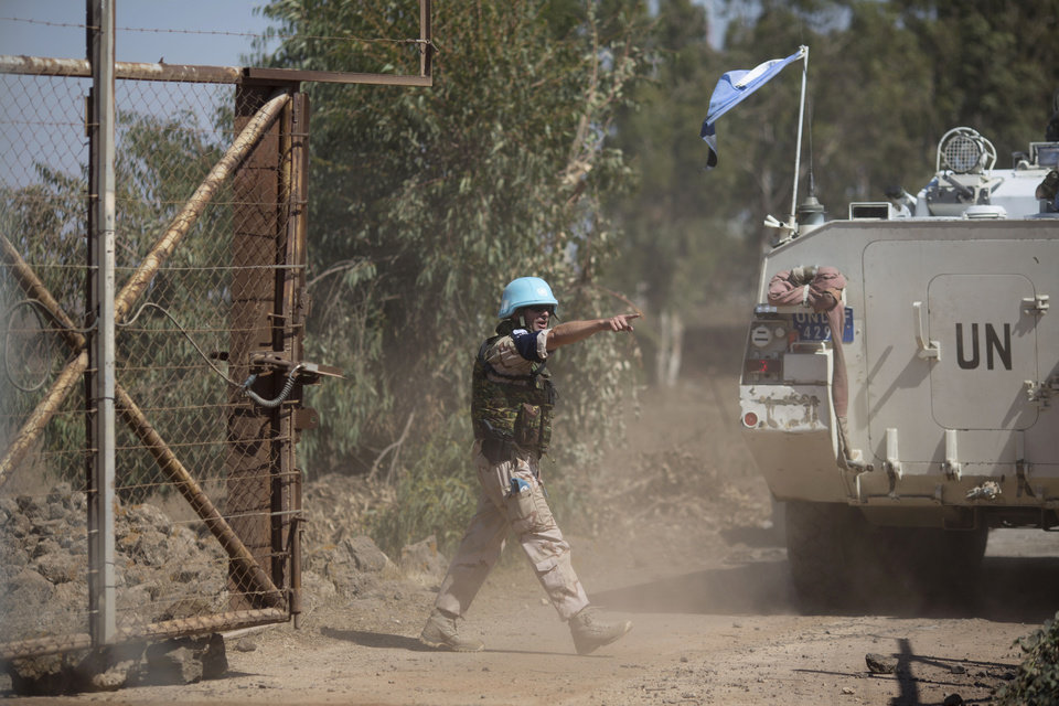 Photo - A UN peacekeeper points as armored vehicles from the U.N. peacekeepers of the United Nations Disengagement Observer Force, also known as UNDOF cross from the Israeli controlled Golan Heights to Syria, Thursday, Aug. 28, 2014.    In southern Syria,  government warplanes targeted rebels near the country's frontier with Israel in the Golan Heights, a day after opposition fighters captured a crossing point on the disputed border.  (AP Photo/Ariel Schalit)
