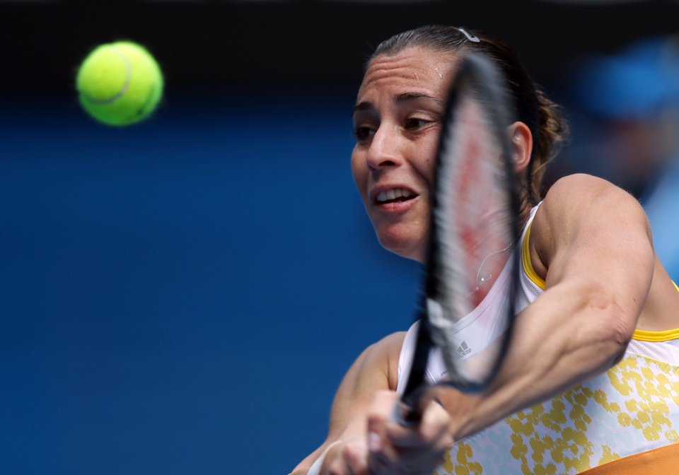 Photo - Flavia Pennetta of Italy makes a backhand return to Angelique Kerber of Germany during their fourth round match at the Australian Open tennis championship in Melbourne, Australia, Sunday, Jan. 19, 2014.(AP Photo/Aaron Favila)