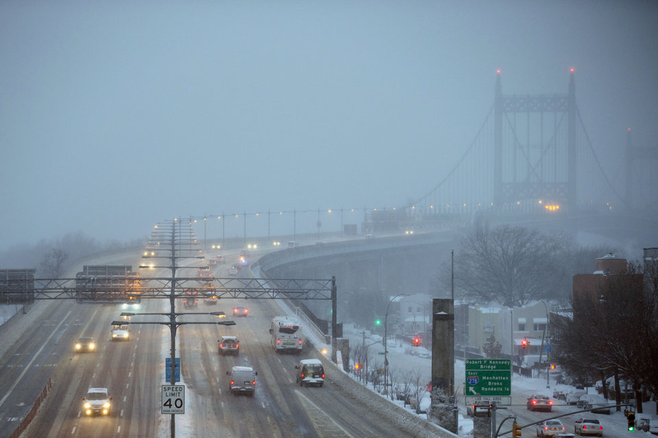 Photo - Traffic crawls through the wind and snow on the RFK Bridge, Friday, Jan. 3, 2014, in the Queens borough of New York. New York City public schools were closed Friday after up to 7 inches of snow fell by morning in the first snowstorm of the winter. (AP Photo/John Minchillo)
